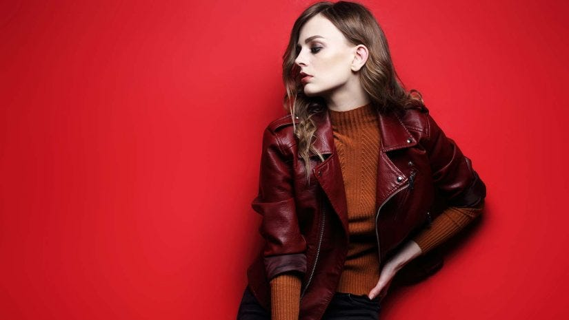 Studio Shot Of Model Wearing Leather Jacket With Red Background