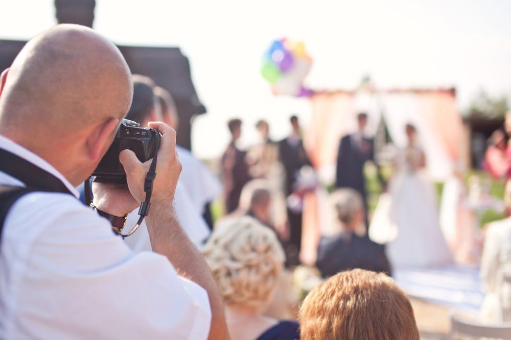 Photographe de mariage gardant la distance à l'aide du zoom