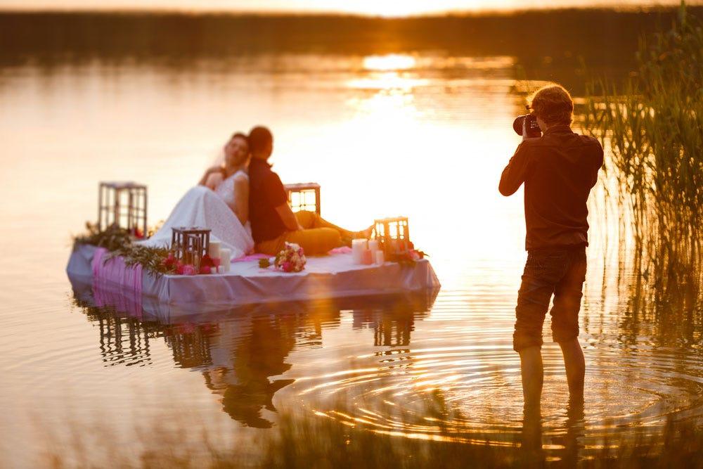 Couple de tir de photographie de mariage sur un radeau au coucher du soleil