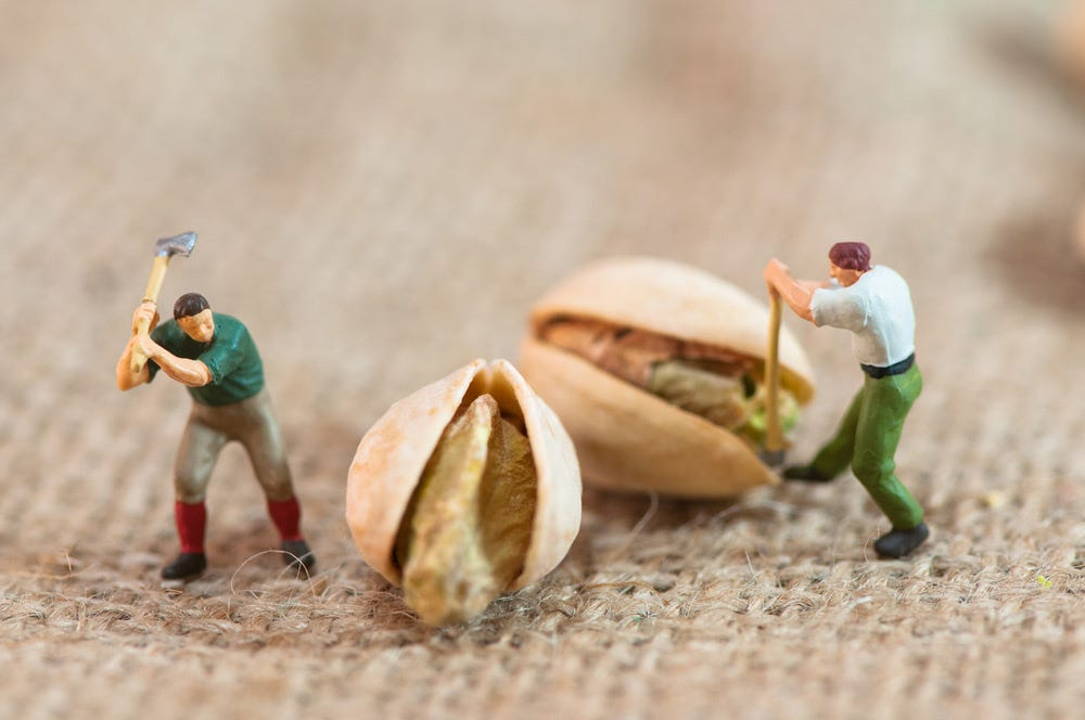 Macro shot of miniature human figures with pistachio nuts