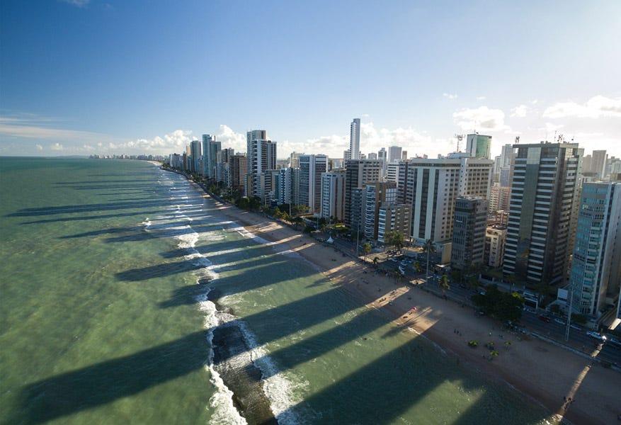 Drone photo de bâtiments projetant de longues ombres sur la plage