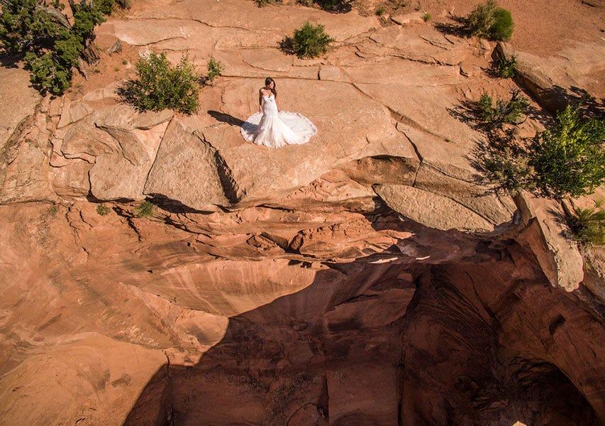 Drone vue aérienne de la mariée en robe de mariée blanche debout sur une falaise