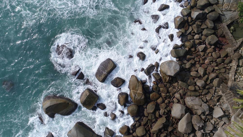 Drone изображение сильных волн, ударяющих по скалам на пляже в Пхукете, Таиланд