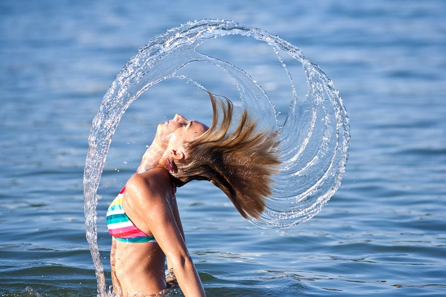 Woman splashing sea water with hair