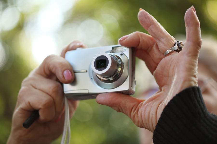 woman holding a point-and-shoot camera for street photography