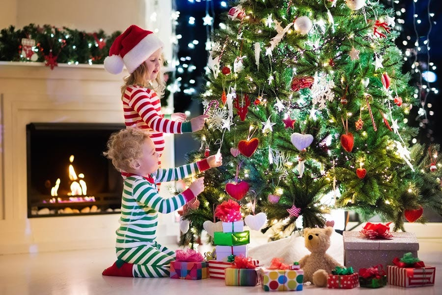 two children in pajamas admiring christmas lights on the tree