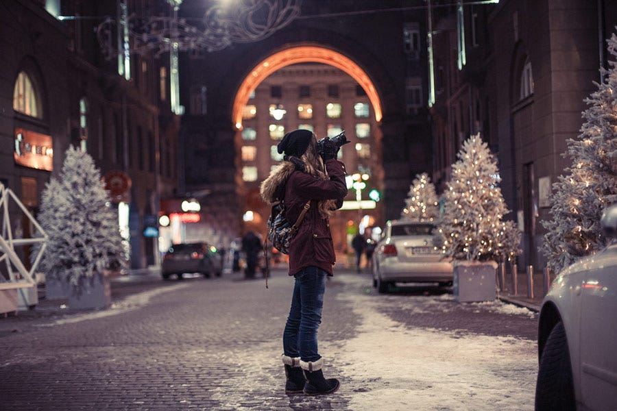 woman shooting street photos in the snow with a professional camera
