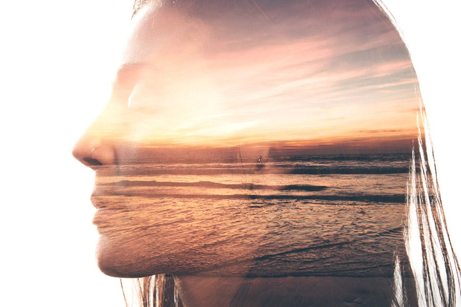 Double exposure of woman and sunset by the beach