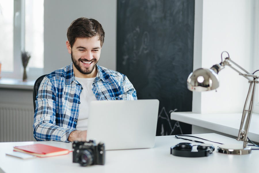 Man smiling while chatting on his laptop