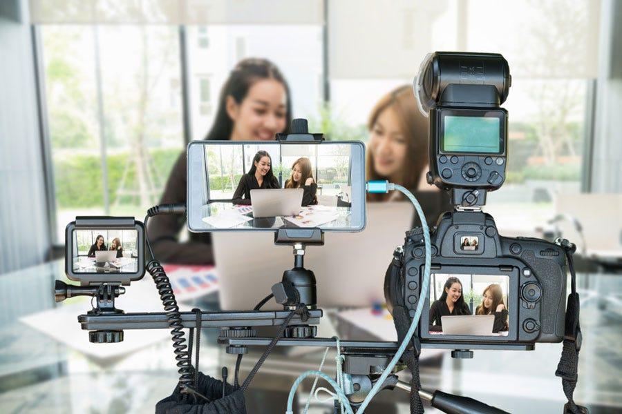 दो एशियाई लड़कियां तीन अलग-अलग प्रकार के कैमरों का उपयोग करके YouTube वीडियो बनाती हैं