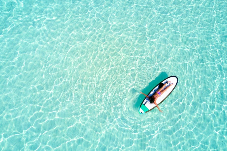 Aerial shot of swimmer on surfboard while in the middle of clear blue waters