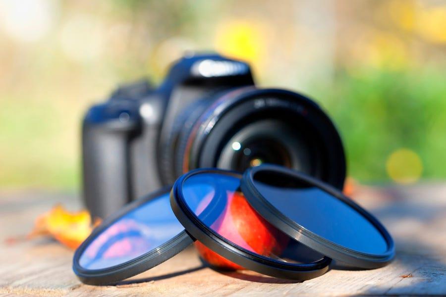surtido de filtros de lentes de cámara apilados frente a una cámara réflex digital