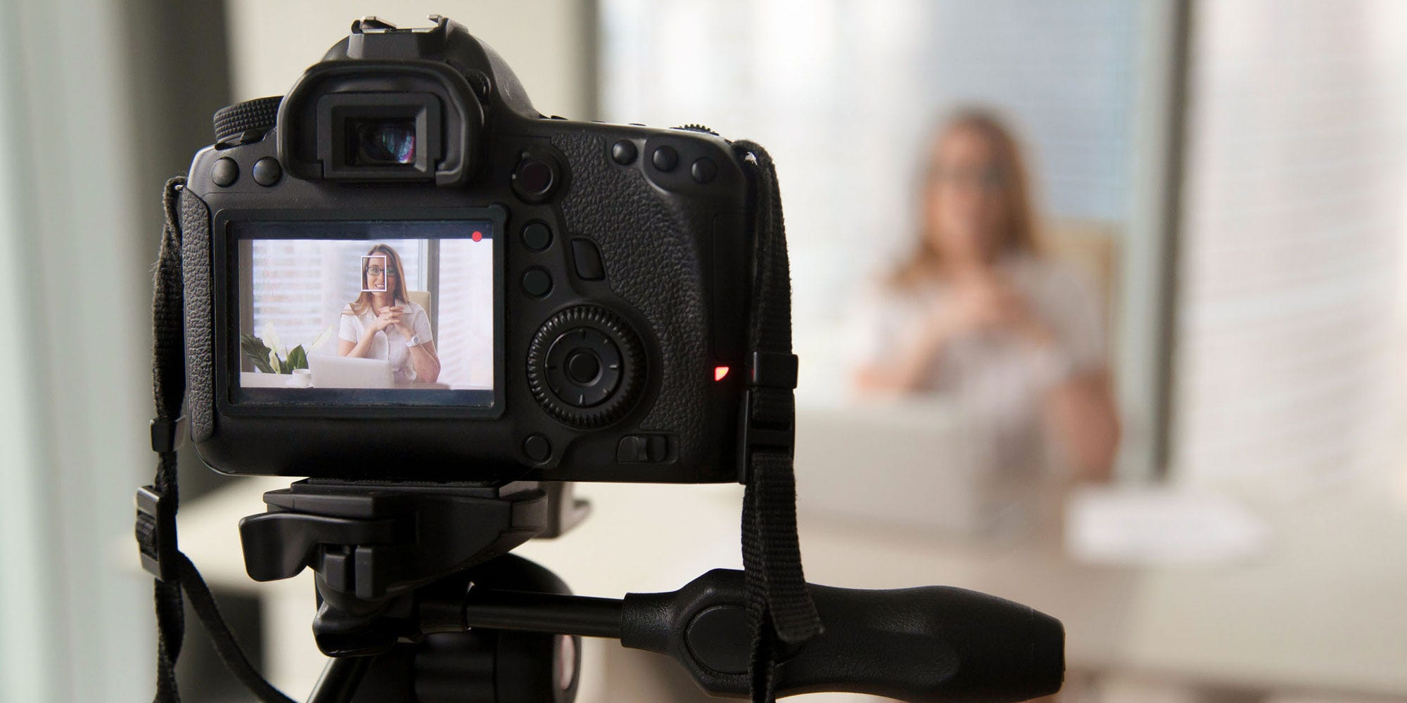 DSLR camera recording woman with blurred background