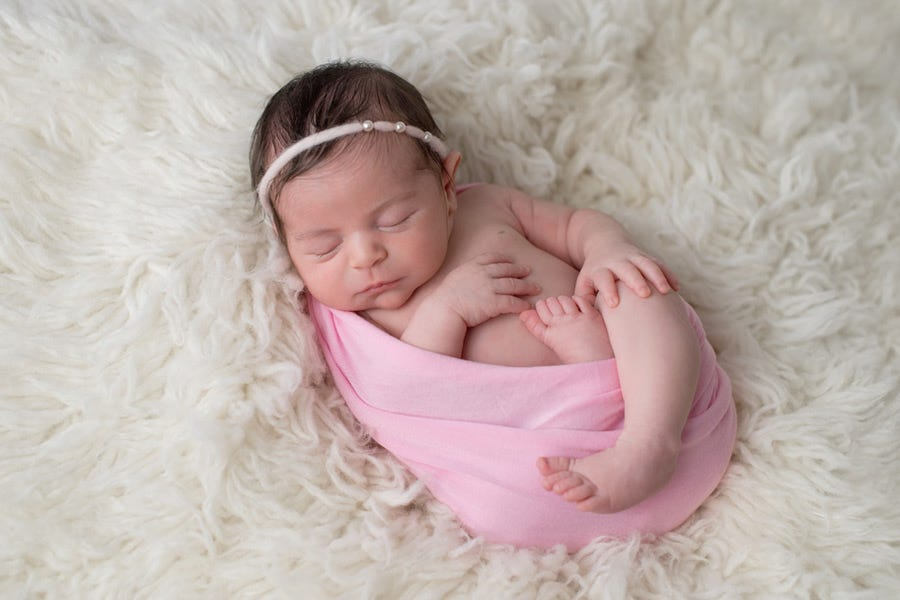 newborn photography shot of adorable sleeping baby girl