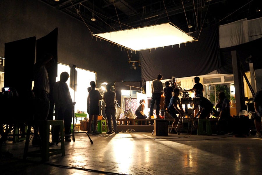 silhouetted shot of film crew on dimly lit set