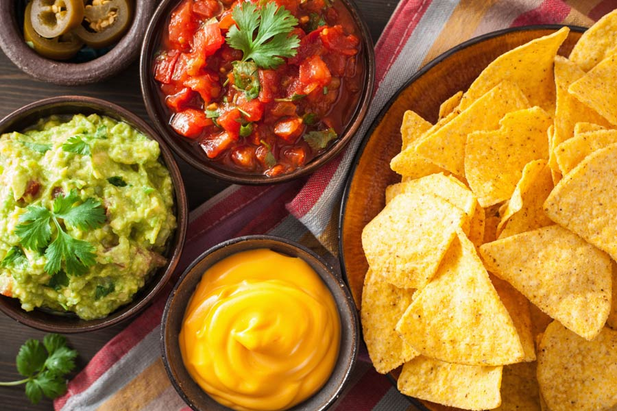 overhead shot of nachos with dips
