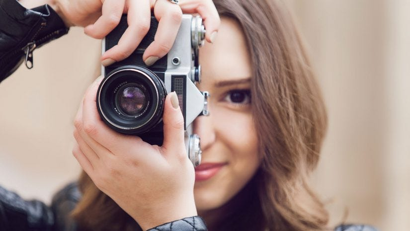 woman aiming with camera in front of her face