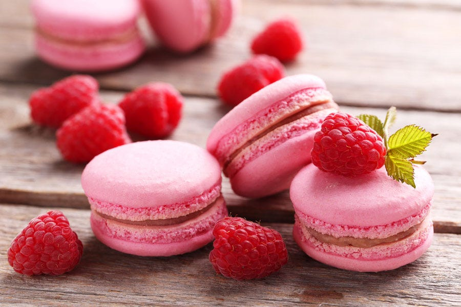 Artistic shot of berries and pink macarons
