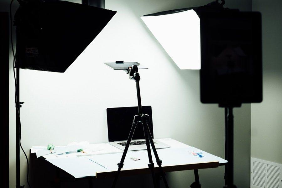 सॉफ्टबॉक्स लाइट एक तिपाई पर लैपटॉप और स्मार्टफोन के साथ एक डेस्क को रोशन करता है