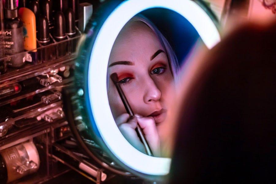 जब वह आईशैडो लगाती है तो एक रिंग लाइट लड़की के चेहरे को चमका देती है