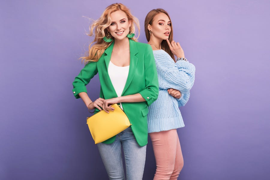two female models in colorful outfits against purple studio background