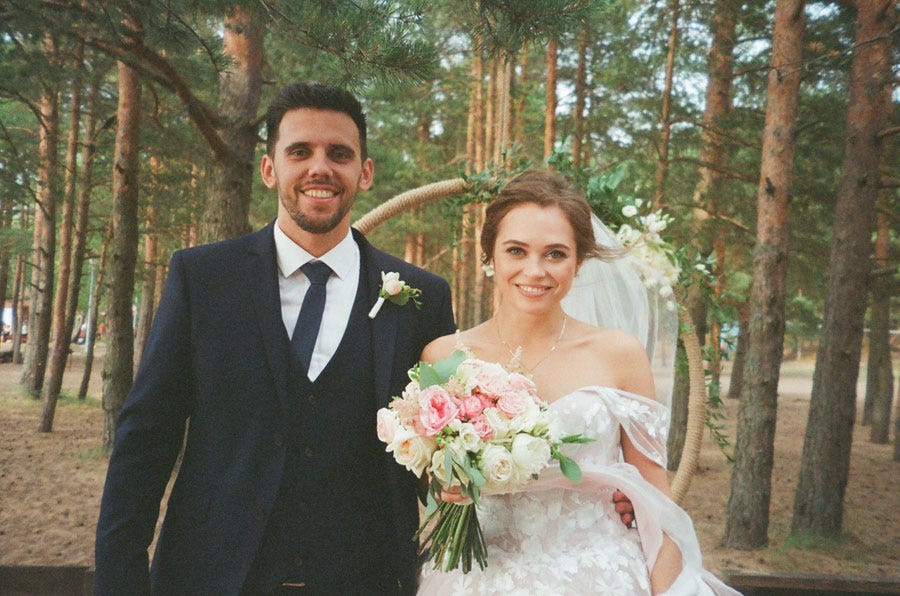 a married couple standing behind trees