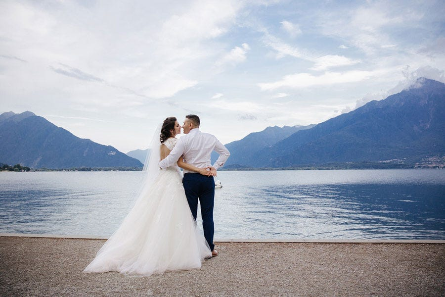 a married couple standing behind a mountain view