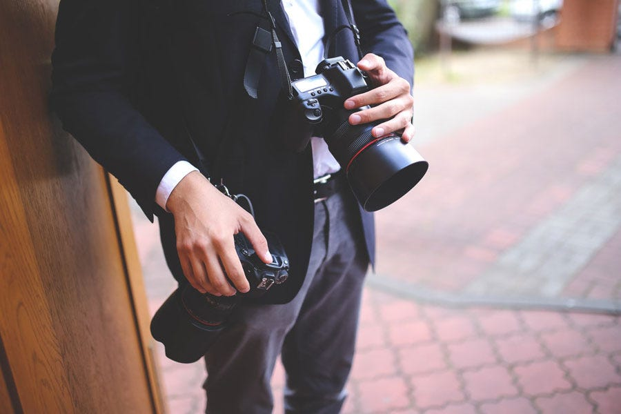 a wedding photographer holding two cameras